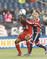 Toronto FC defender Doneil Henry (4) heads the ball in the penalty area and fends off New England Revolution midfielder Diego Fagundez (14). In a Major League Soccer (MLS) match, the New England Revolution (blue) defeated Toronto FC (red), 2-0, at Gillette Stadium on May 25, 2013.