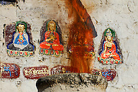 Flames from an incense burner at a wall shrine, with painted figures of Buddhist deities and Tsongkhapa, founder of Gelugpa Yellow Hat sect, on the Barkhor pilgrim circuit, Lhasa, Tibet.