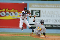 Asheville Tourists shortstop Rosell Herrera #29 makes a throw to first over a hard sliding Kirk Singer during a game against the West Virginia Power  at McCormick Field on June 10, 2012 in Asheville, North Carolina . The Tourists defeated the Power 13-3. (Tony Farlow/Four Seam Images).