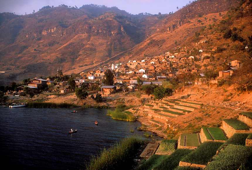 Beside Lake Atitlan  is the Kaqchikel town of San Antonio Palopo with a population of 2650. Both men and women still wear traje. Women wear backstrap loomed red striped huipiles, red head ribbons, and blue skirts. Men dress in similar striped shirts and pants with a small woolen blanket called a rodillera around the hips. The men raise onions and anise in terraced fields beside the lake and fish is small boats..Photograph by Peter E. Randall