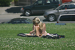 YOUNG WOMAN RELAXES on LAWN with a GOOD BOOK