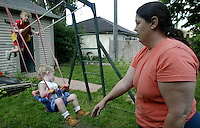 Foster parent Bobbi Pedersen, right, pushes her foster child Christopher Gray, center, and adopted daughter Aleah Pederson on the swings in their backyard Monday June 16, 2003 in Columbus, Ohio.<br />