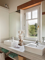 Two heavy basins are set on a shelf unit in the neutral bathroom.