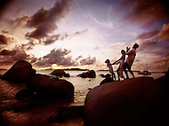 A family walks on top of large rocks that are found all over the coast of the British Virgin Islands