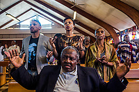 SOWETO, JOHANNESBURG, SOUTH AFRICA - DECEMBER 08: Parishioners offer prayers during Sunday mass at the Regina Mundi Roman Catholic church in Soweto on December 8, 2013 in Johannesburg, South Africa. Mr Mandela, died on Thursday aged 95, spent 27 years in jail before becoming South Africa's first black president in 1994.<br /> Photo by Daniel Berehulak for The New York Times