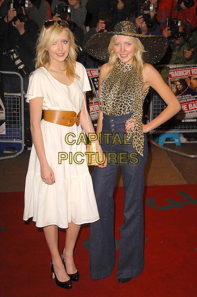 """SAMANTHA MARCHANT & AMANDA MARCHANT.""""The Bank Job"""" - UK film premiere.Odeon West End, London, England..February 18th, 2008 .full length Sam Samanda the Twins Big Brother sisters siblings cream white dress brown belt blue denim jeans flared wide leg trousers high waisted black hat 70's seventies style clothes bag hand on hip leopard print ruffle blouse top shirt .CAP/CAS.©Bob Cass/Capital Pictures."""