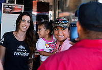 Sept. 21, 2013; Ennis, TX, USA: NHRA funny car driver Alexis DeJoria (left) poses for a picture with some fans during the Fall Nationals at the Texas Motorplex. Mandatory Credit: Mark J. Rebilas-