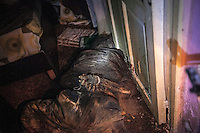 In this Monday, Dec. 10, 2012 photo, a man's dead body tightened by hands allegedly executed and abandoned lies inside a residential house after it was discovered by Syrian rebels when they carried out a raid in the battlefield of Aleppo, Syria. (AP Photo/Narciso Contreras)