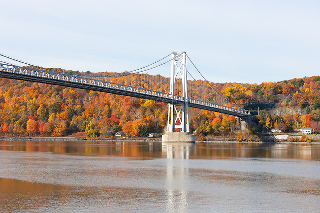 The Mid-Hudson Bridge spans the Hudson River between Poughkeepsie and Highland, New York with fall foliage in the background.
