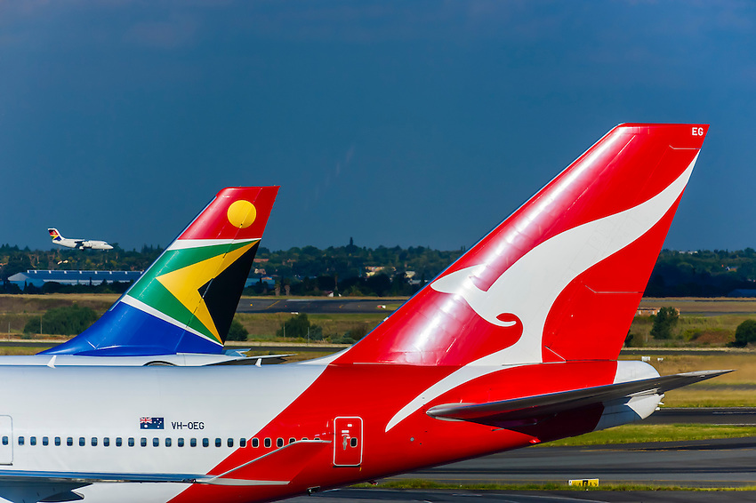 Quantas Boeing 747-438 airplane with the tail of a South African Airways jet behind it, O. R. Tambo International Airport, Johannesburg, South Africa.