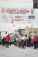 Mark Selland and team leave the ceremonial start line with an Iditarider at 4th Avenue and D street in downtown Anchorage, Alaska during the 2015 Iditarod race. Photo by Jim Kohl/IditarodPhotos.com