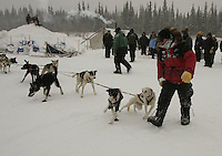 Doug Swingley leads his dogs to a parking spot at the Nikolai checkpoint