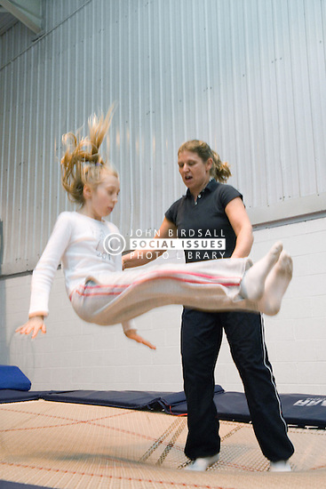 Visually impaired person with teacher at trampolining youth group event run by NRSB,