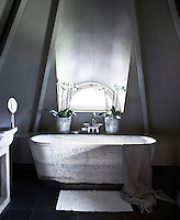 The tranquil bathroom, nestled under the eaves, has been created with a marble bath and a stone-tiled floor