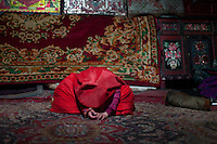 A young Kyrgyz girl falls asleep on the floor, exhausted..Camp of Manara (Sufi camp), near the borders with China and Tajikistan...Trekking with yak caravan through the Little Pamir where the Afghan Kyrgyz community live all year, on the borders of China, Tajikistan and Pakistan.