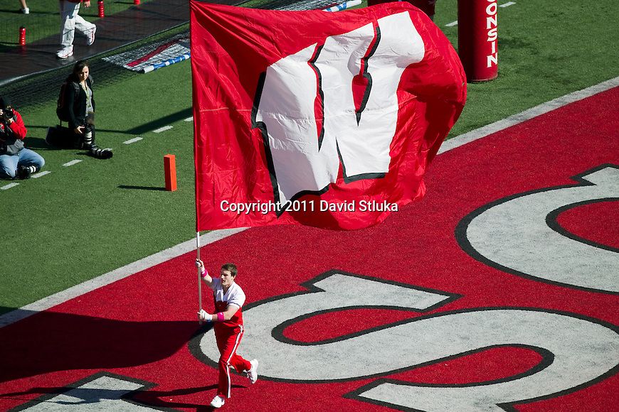 Wisconsin Badgers cheerleader carries a flag across the field after a touchdown during an NCAA Big Ten Conference college football game against the Indiana Hoosiers on October 15, 2011 in Madison, Wisconsin. The Badgers won 59-7. (Photo by David Stluka)