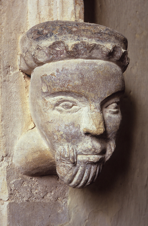 Simple 16th century stone corbel carving of head of man with beard and soft hat in church in Norfolk East Anglia England UK