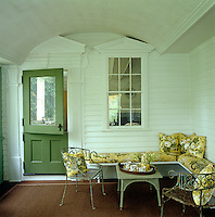 A chintz-covered banquette, some wrought iron chairs and a rattan coffee table have been arranged in one corner of the painted weatherboard porch