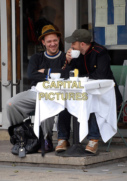 WILL YOUNG & FRIEND.Enjoying a coffee on Great Portland Street, London, England, UK, .October 30th 2009..full length sitting table cafe outside drink grey gray tracksuit bottoms ripped hole jumper top cap hat  sweater .CAP/IA.©Ian Allis/Capital Pictures