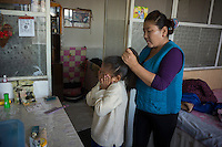 Mongolian herder Renqima arranges the hair of granddaughter Dula before she went to school in Damao Banner, Inner Mongolia, China, October 2014.