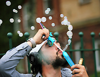 Pictured: A man blows bubbles exhaling smoke from an electrinic cigarette outside the Palace Theatre in Swansea. Sunday 16 July 2017<br />