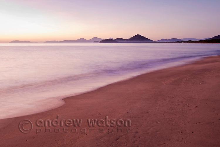 View along beach at dawn.  Machans Beach, Cairns, Queensland, Australia