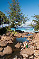 Woman sitting on boulder in Hanakapiai creek at Hanakapiai Beach, Napali Coast, Kauai, Hawaii