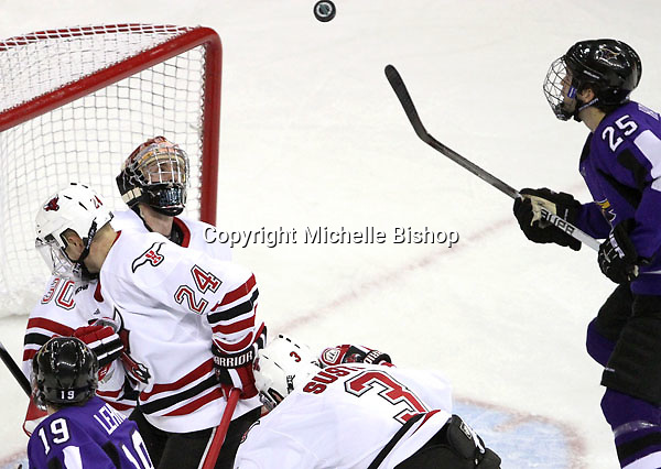 Minnesota State University-Mankato's Eriah Hayes and UNO goalie John Faulkner focus on a highflying puck. (Photo by Michelle Bishop)