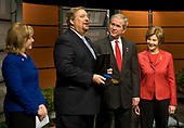 Rick Warren, left, presents the P.E.A.C.E. medal  to United States President George W. Bush as they participate in Saddleback Civil Forum on Global Health at the Newseum in Washington, D.C., Monday, December 1, 2008. Looking on are First Lady Laura Bush, right, and Kay Warren, left.<br /> Credit: Mannie Garcia / Pool via CNP