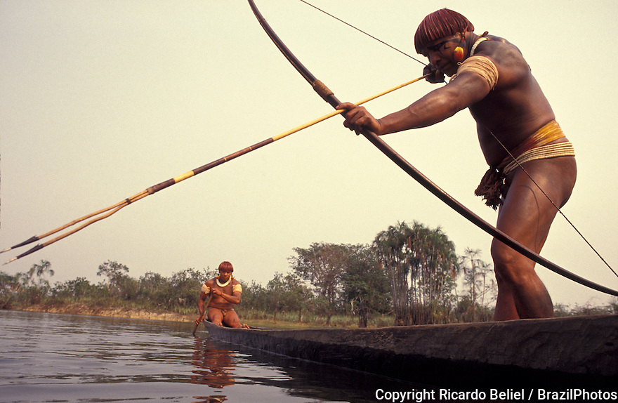 Body-painted Yaulapiti indigenous People in canoe fishing with bow and arrow at Tuatuari river - daily life in Xingu National Park, Amazon rainforest, Brazil.