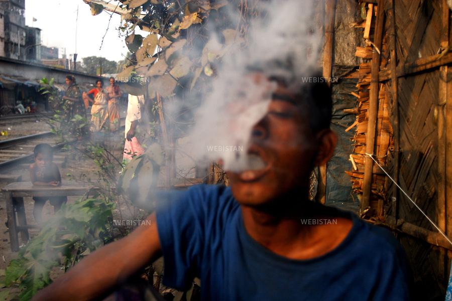 2006. Bangladesh, Dhaka. Marijuana user in a slum. .Marijuana is still the most popular addictive substance in widespread use in Bangladesh but the marijuana smoked today is said to be 15 times more potent than that smoked in the 60s. The result is that those who smoke it have significantly more respiratory symptoms like chronic cough and mucus production, wheezing, and acute bronchitis, than previously..2006. Bangladesh, Dhaka. Consommateur de marijuana dans un bidonville. .La marijuana est encore la substance additive la plus populaire de grande consommation au Bangladesh, mais on dit que la marijuana fumée aujourd'hui est dix fois plus puissante que celle fumée dans les années 60. Par conséquent ceux qui la fument ont beaucoup plus de troubles respiratoire comme par exemple des toux chroniques et production de mucus, des poumons sifflant et des bronchites aigues qu'avant..