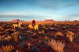 USA; Arizona; Utah, Monument Valley, Navajo Tribal Park, a Navajo man and his son ride on horseback, looking towards Bringham's Tomb in Utah