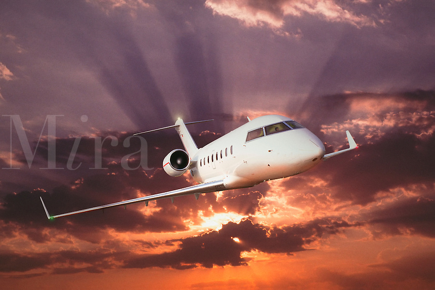 Twin  engined executive jet flying out of a dramatic sunburst
