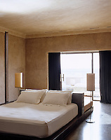A leather-upholstered inverse T-frame supports a bed on one side and a sofa on the other in this minimal bedroom