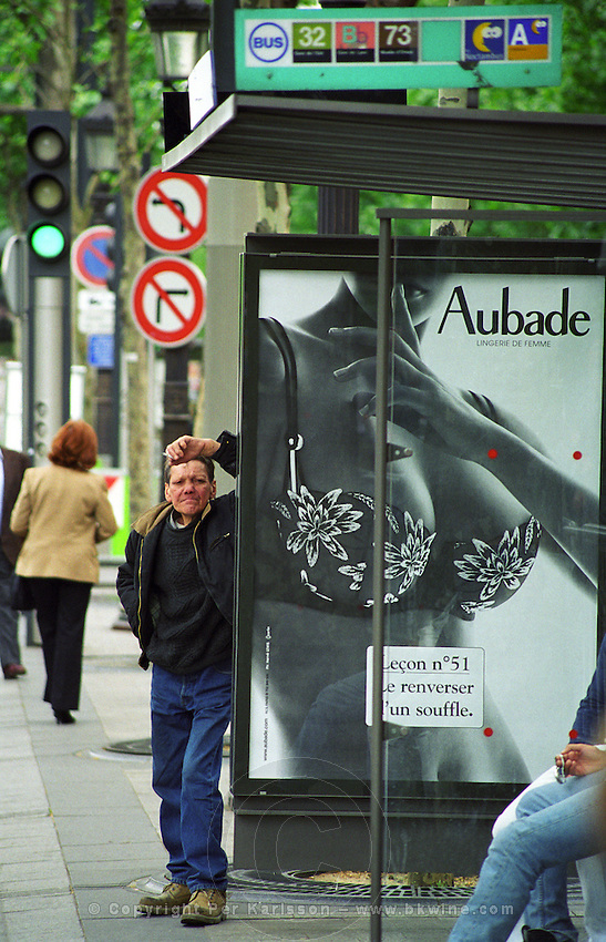 A man standing leaning on a bus shelter on the Avenue des Champs Elysees. An advertisement for Aubade showing a woman naked except for a bra brassiere with full round breasts opulent bosom. The man looks run down and tired, perhaps a street walker, and is smoking a cigarette the naked woman is holding up a finger to her lips as to say hush. Street signs and pedestrians in the background. Paris, France, Europe