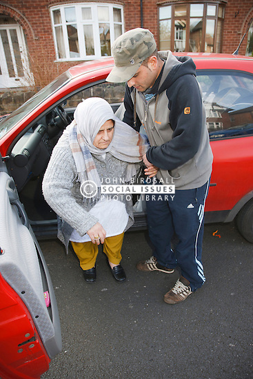 Elderly south Asian woman being helped out of a car by her son.