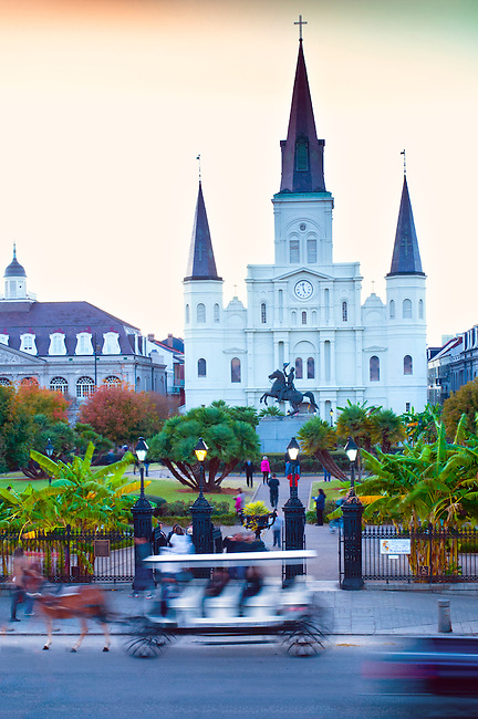 Horse drawn carriage is a blur at sunset in front of the gates to Jackson Square in the French Quarter of New Orleans. The St. Louis Cathedral dominates the architecture of the public park that was named after President Andrew Jackson whose equestrian statue can be seen in front of the church.