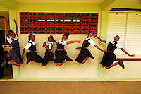 Barbados, Farmers, view of six school girls in school uniform enjoying by jumping in front of wall while their teacher standing by them at the school Few years ago photographers Anthony Asael and Stepahnie Rabemiafara dreamed a dream that seemed quite imposible: to visit every country of the World promoting arts and tolerance among children and, of course, taking photographs of them. With little money and resources but an impressing will, the duo got an astonishing goal. In four years they visited 300 schools in 192 countries where kids participating of the project created 18,000 pieces of artwork. <br />