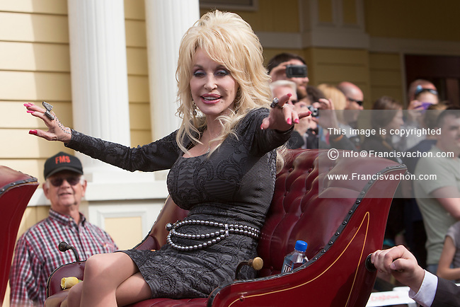 Dolly Parton waves to the crowd as she rides a horse carriage during the parade of the Festival of Nations is pictured in Dollywood theme park in Pigeon Forge, Tennessee Friday March 21, 2014. Located in the Knoxville-Smoky Mountains metroplex, Dollywood is a theme park owned by entertainer Dolly Parton and Herschend Family Entertainment.