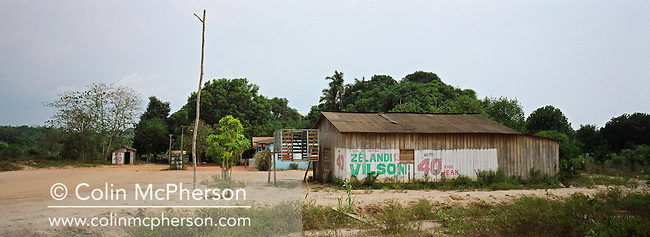 A shanty town with political graffiti painted on the buildings, one of many which have sprung up along Highway BR163 as the population changes due to changing agricultural practices in the area. The highway ran from Santarem on the banks of the Tapajos river for one thousand miles south into the state of Mato Grosso and was unpaved except for a small stretch at its northern end. The area surrounding the highway was the front line in the battle between local communities and environmentalists who tried to prevent to spread of rainforest destruction by illegal loggers and companies which bought and seized land for use in cattle ranching and growing soy beans for export from Brazil via the port at Santarem.