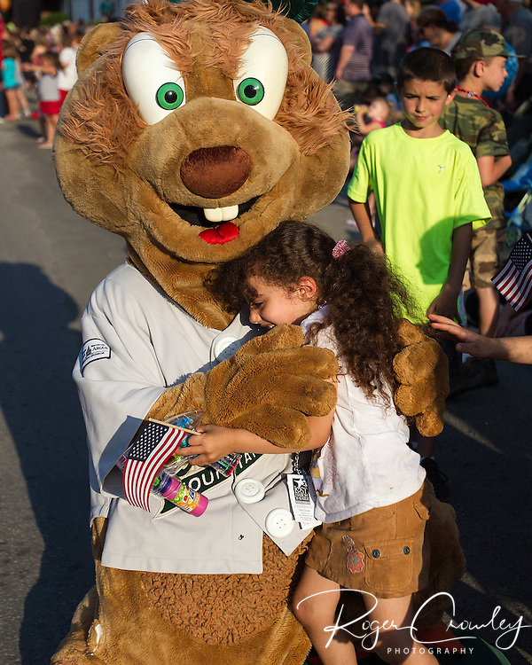 Elaria Joseph from Egypt give SKIP the Vermont Mountaineer mascot a hug during the July 3rd Parade in Montpelier Vermont 2013.