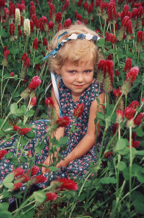 Little girl sitting in clover, with hair ribbons
