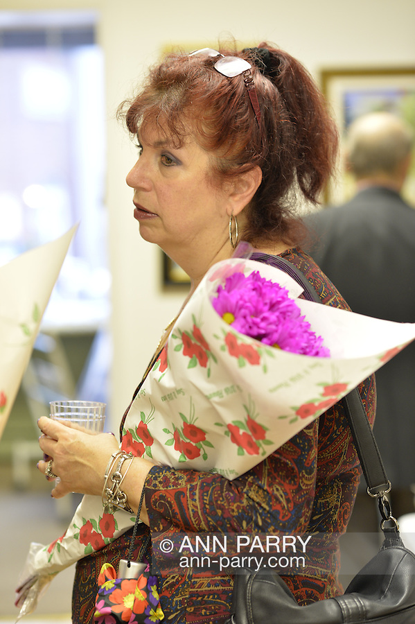 Port Washington, New York, U.S 6th October 2013.  Artist holding bouquet of flowers at The Artists Reception for Members Showcase of the Art Guild of Port Washington, at The Graphic Eye Gallery.