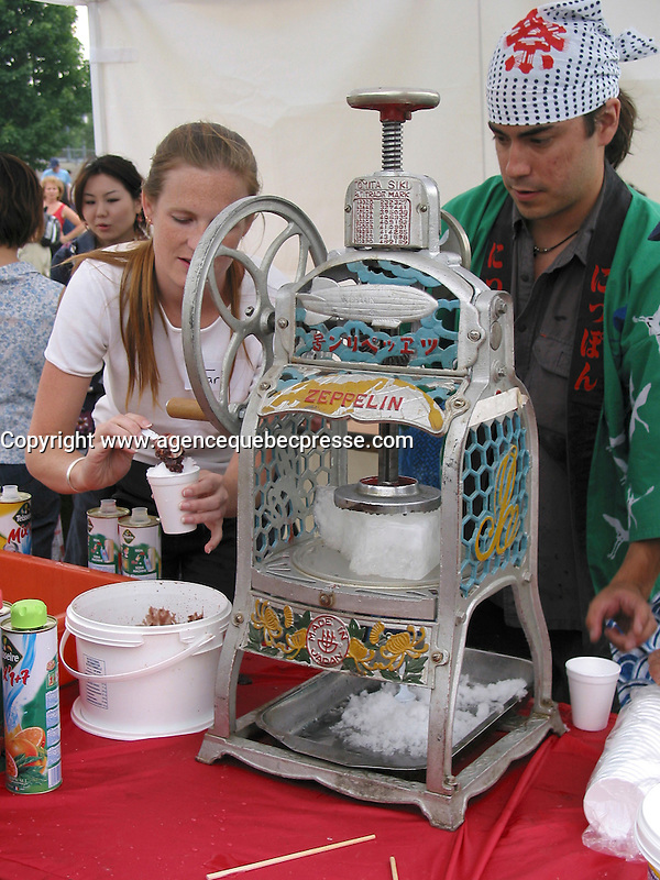 July 6  2002, Montreal, Quebec, Canada<br /> <br /> Volunteer prepare a traditional Japanese refresment, made of ice and fruit syrup<br /> , during the Matsuri one day Japanese Festival in Montreal Old Port, Juy 6 2002.<br /> <br /> The event feature demonstration of Japanese traditional martial art, music, food and other activities.<br /> <br /> <br /> <br /> Mandatory Credit: Photo by Pierre Roussel- Images Distribution. (&copy;) Copyright 2002 by Pierre Roussel <br /> <br /> NOTE :<br /> Canon G-2 oroginal jpeg, converted from sRG to  Adobe 1998 RGB.<br /> Original size and uncompressed file available on request.