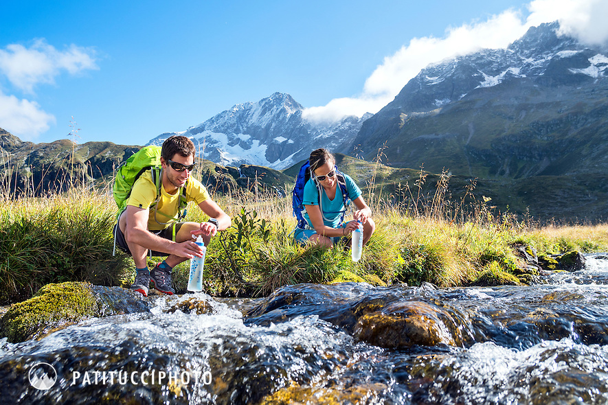 Hikers stopped at a mountain creek to fill their water bottles which have a water filter system built into the top, while hiking the Tour du Mont Blanc