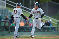 Dylan Moore (6) of the Hickory Crawdads slaps hands with third base coach Steve Mintz (13) after hitting a solo home run in the top of the 1st inning against the Kannapolis Intimidators at Kannapolis Intimidators Stadium on April 8, 2016 in Kannapolis, North Carolina.  The Crawdads defeated the Intimidators 8-2.  (Brian Westerholt/Four Seam Images)