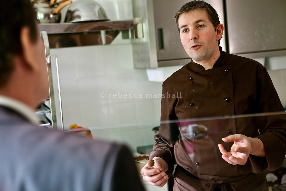Chocolatier Patrice Arbona talks to a customer as he makes chocolate in his shop 'Entre Mes Chocolats', Vence, France, 10 February 2011