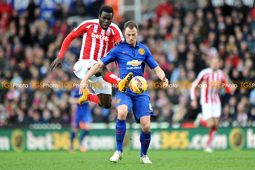 Mame Biram Diouf of Stoke City vies for the ball with Jonny Evans of Manchester United - Stoke City vs Manchester United - Barclays Premier League Football at the Britannia Stadium, Stoke-on-Trent - 01/01/15 - MANDATORY CREDIT: Greig Bertram/TGSPHOTO - Self billing applies where appropriate - contact@tgsphoto.co.uk - NO UNPAID USE