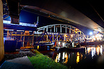NIEUWEGEIN -  In het holst van de nacht heeft Rijkswaterstaat door Civiele Technieken deBoer – Spanlift een tijdelijke hulpbrug vanaf een ponton op de plaats van de weggeschoven Jutphasebrug over het Amsterdam-Rijnkanaal getakeld. De uit 1936 daterende boogbrug krijgt door bouwcombinatie KWS-Mercon een opknapbeurt en is een avond eerder op hoge hulppijlers verschoven waar later de stalen constructie versterkt, brugdek en pijlers gerepareerd en de brug opnieuw geverfd wordt. De Jutphasebrug zal naar een ontwerp van ingenieursbureau Movares volgend jaar 45 cm hoger worden teruggeschoven om hoger containervaart eronder mogelijk te maken. De renovatie van de Jutphasebrug is onderdeel van het project KARGO(Kunstwerken Amsterdam-Rijnkanaal Groot Onderhoud) waarbij acht stalen bruggen over het Amsterdam-Rijnkanaal, Lekkanaal en Buiten-IJ worden gerenoveerd en verhoogd. COPYRIGHT TON BORSBOOM