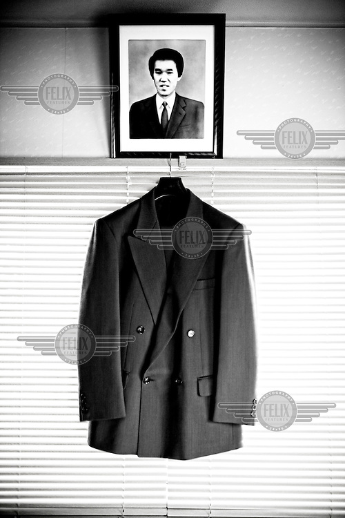 "A jacket that belonged to Akira Teranishi is seen with his photo in Kyoto. Akira was a restaurant manager and worked 12-14 hours a day for more than 10 years. His excessive overwork and stress brought depression on him eventually and he ended his life by jumping from a building on a snowy Valentine's Day. ""Pain never goes away no matter how much time passes. After my husband's death, children grew up, got married, and grandchildren were born. More things to celebrate in my life, more sadness I feel, because I always wished my husband was here with me to share joy."" says his wife Emiko.."